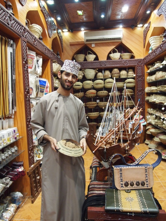a shopkeeper in the souq wearing traditional Omani dress: dishdasha & kumah
