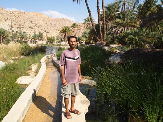 Adil stands on the falaj leading to Wadi Bani Khalid