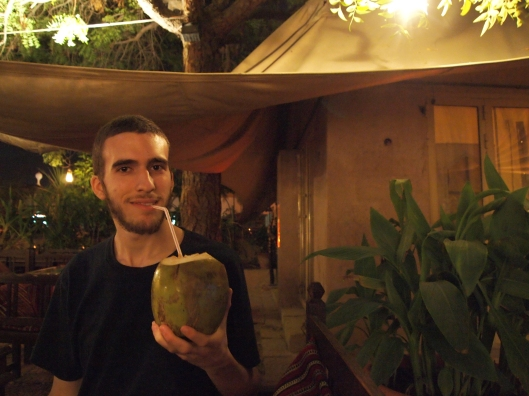 Alex with a coconut drink in a coconut shell