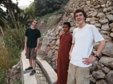 Alex, Ahmed and Adam stand on the falaj going down to Wadi Tiwi in Oman