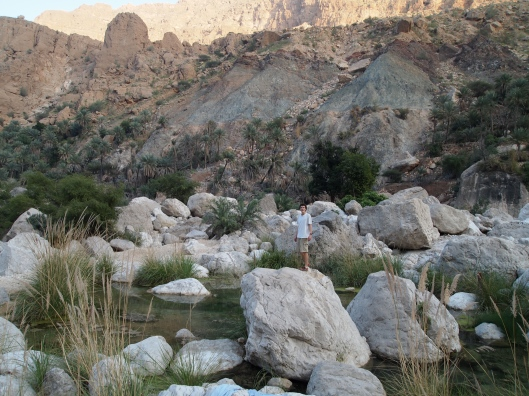 Adam stands on a big boulder in the pools of Wadi Tiwi
