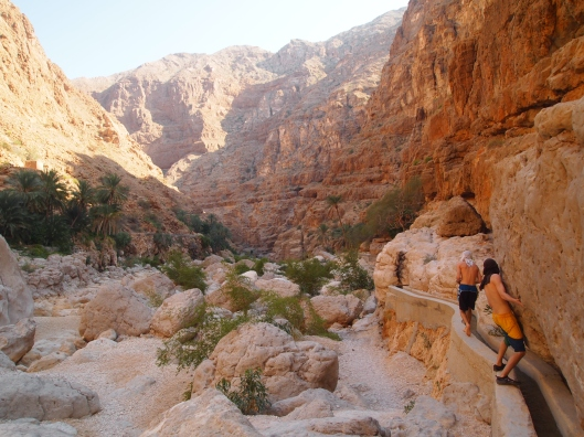 Alex and Adam climb along the edge of the falaj