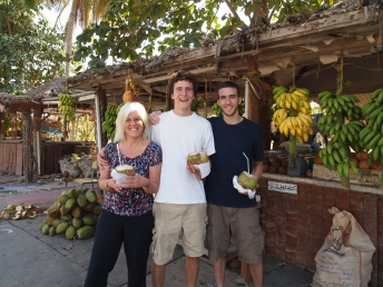 drinking coconut juice at a Salalah fruit stand ~ Oman