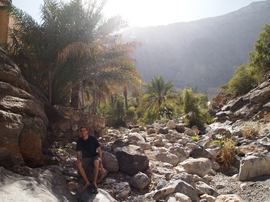 Alex sits on a rock to put his shoes on in the canyon leading to Balad Sayt