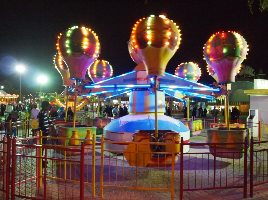 colorful spinning rides at the amusement park