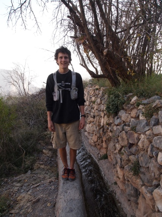 Adam in Oman, standing on the edge of a falaj