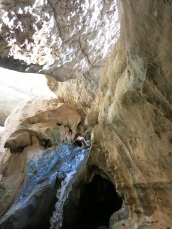 inside the cave, the boys climb up a rope by the waterfall