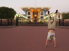 Adam does a handstand in front of Al Alam Palace