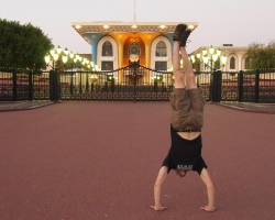 Alex does a handstand in front of Al Alam Palace