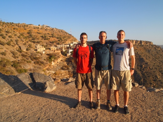 Alex, Mike and Adam with a village behind