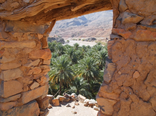 view of the plantations through a door in the ruined village