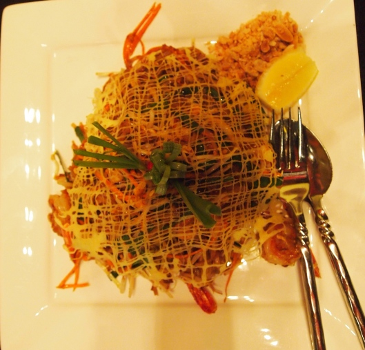 Pad Thai with Prawns with eggs drizzled and cooked on top in an artistic pattern
